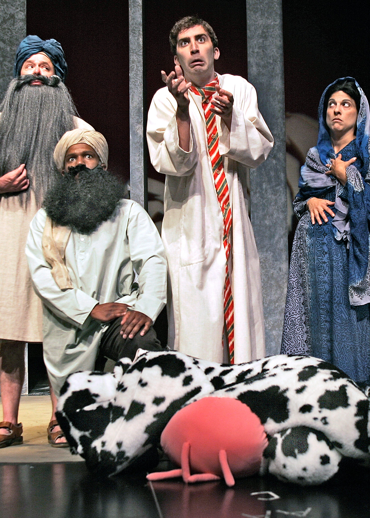 Four shocked actors in Eygtipian costumes standing over an actor in a cow costume laying on the ground