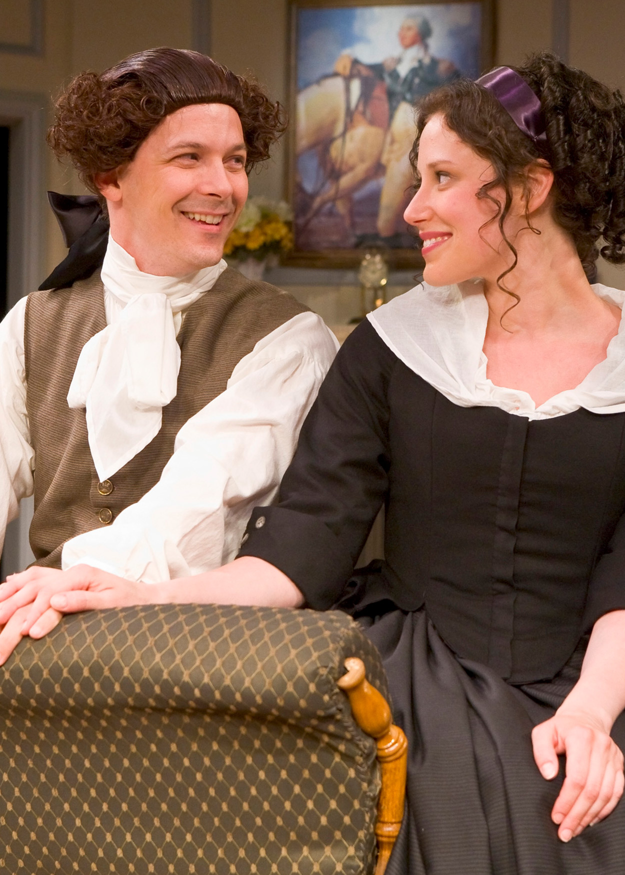 man and woman in colonial dress smile at each other