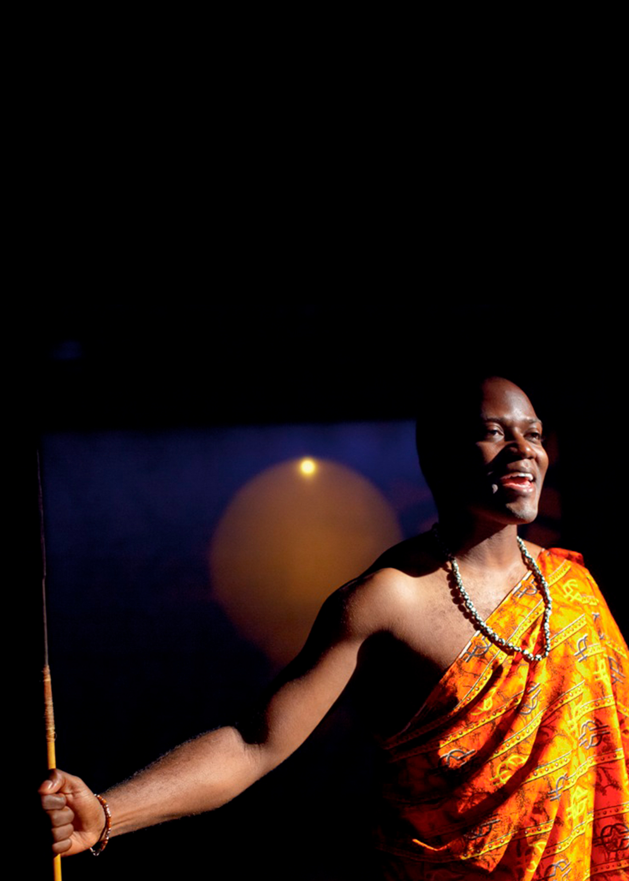 African American male wearing a bright yellow African sarong arms open