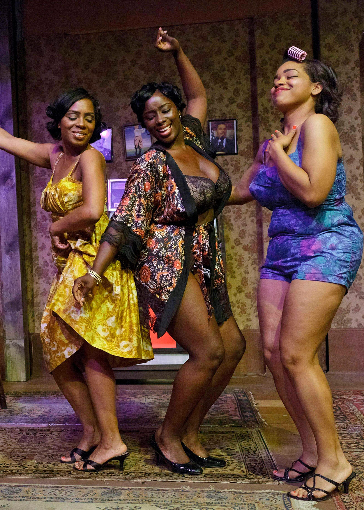 Three African American women dancing in a living room