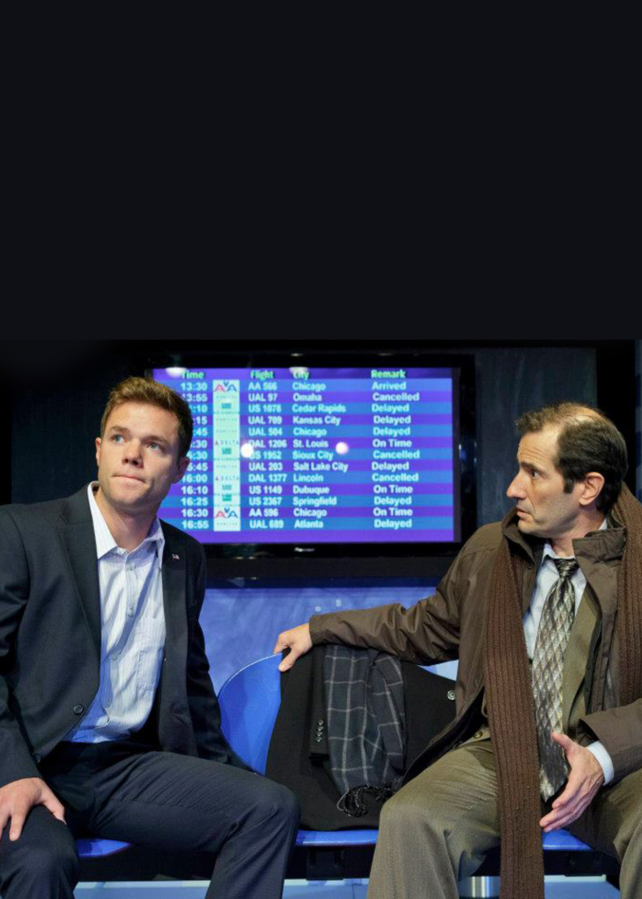 Two men sit inside an airport, a flight departure screen is behind them