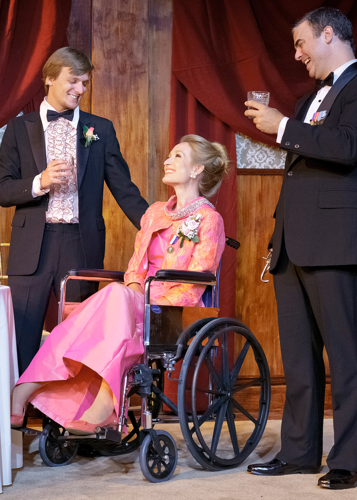 A woman in a pink dress sitting in a wheelchair between two standing men in tuxedos