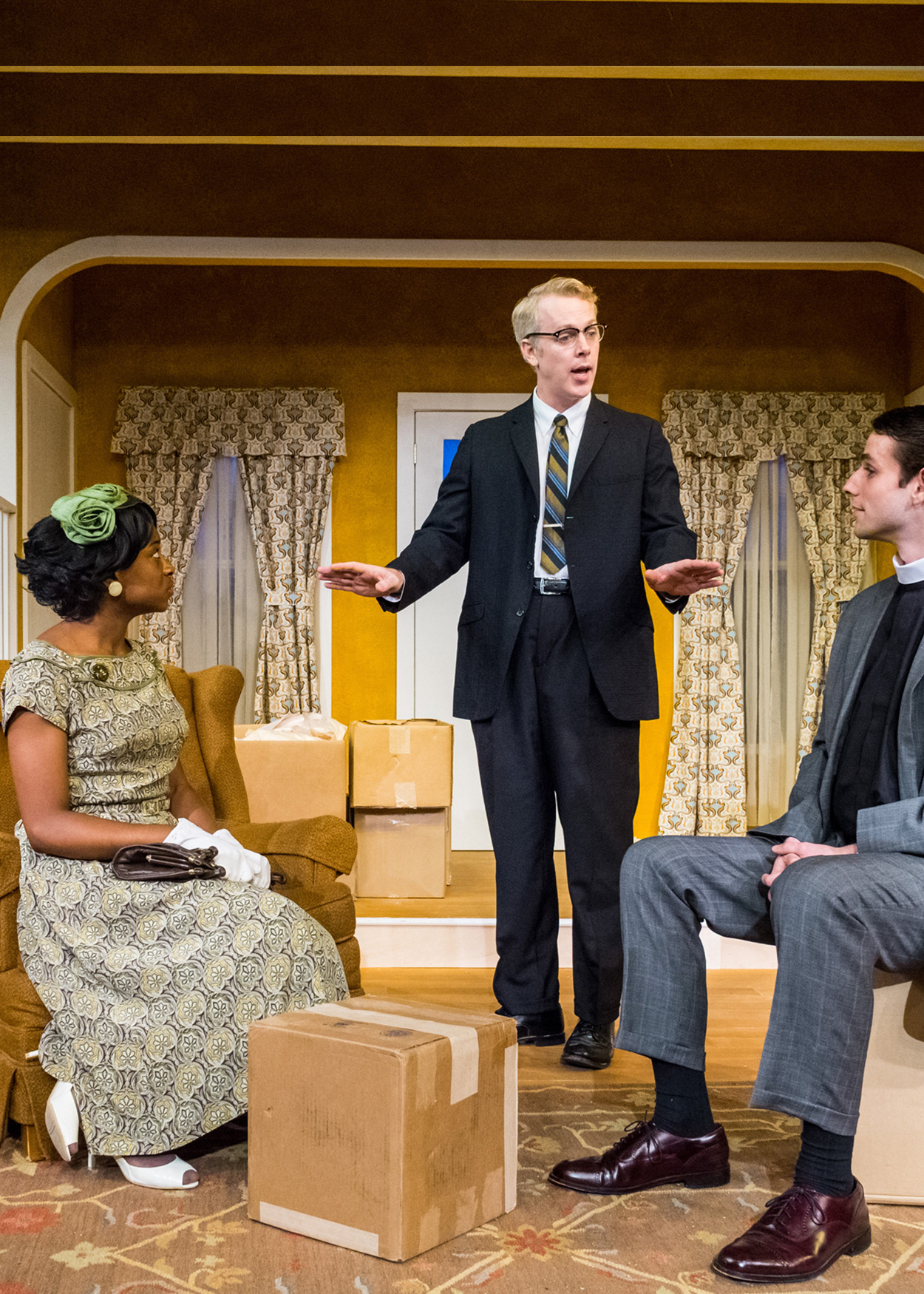 Production Photo from Clybourne Park (2013). The set is a living room in 1959. A black man stands in the back left corner, a black woman its in a chair, a white male stands in the center and a white priest sits on a box.