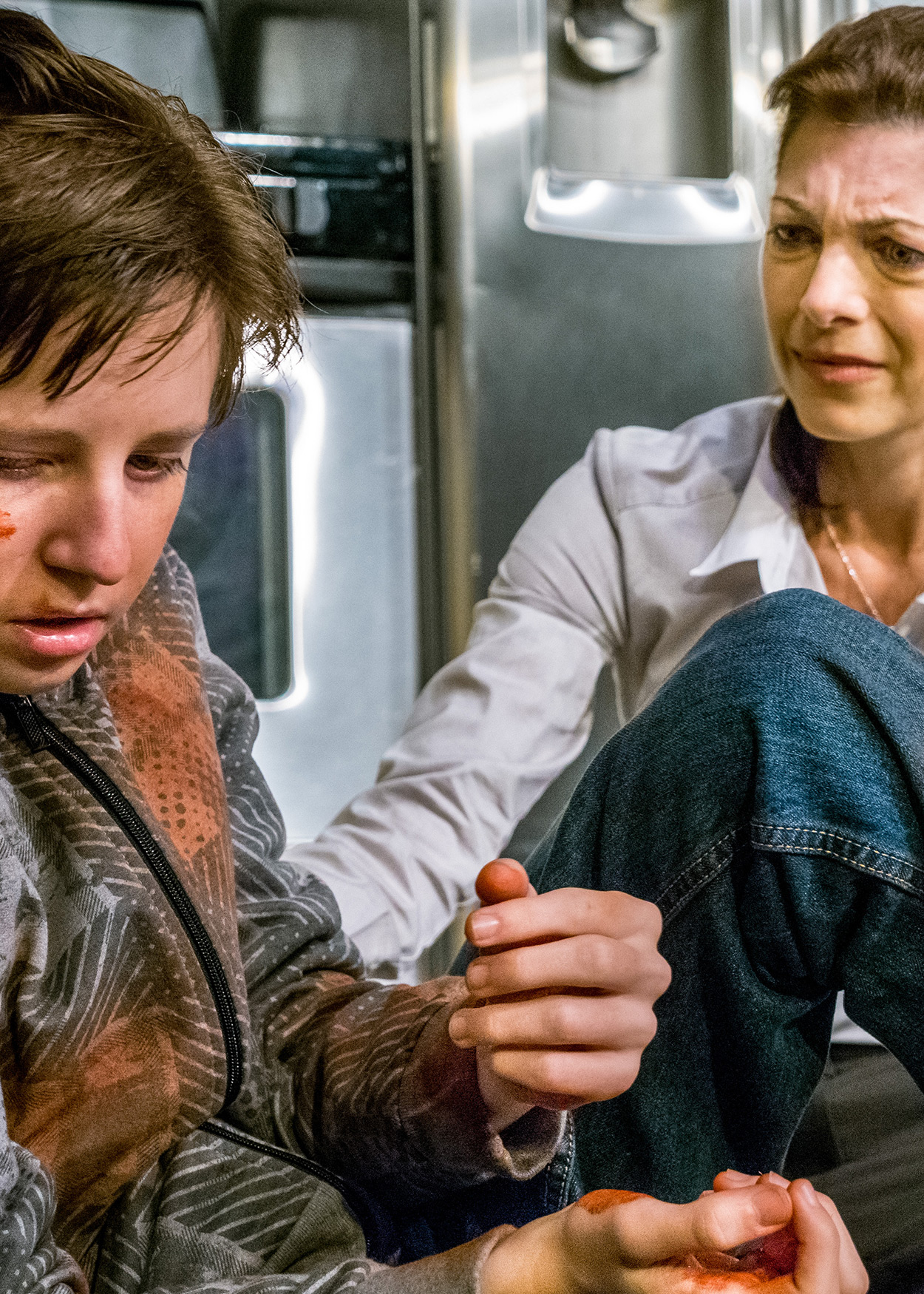Production Photo from The Beautiful Dark (2013). A wounded boy sits on the floor of a kitchen and an older woman comforts him.