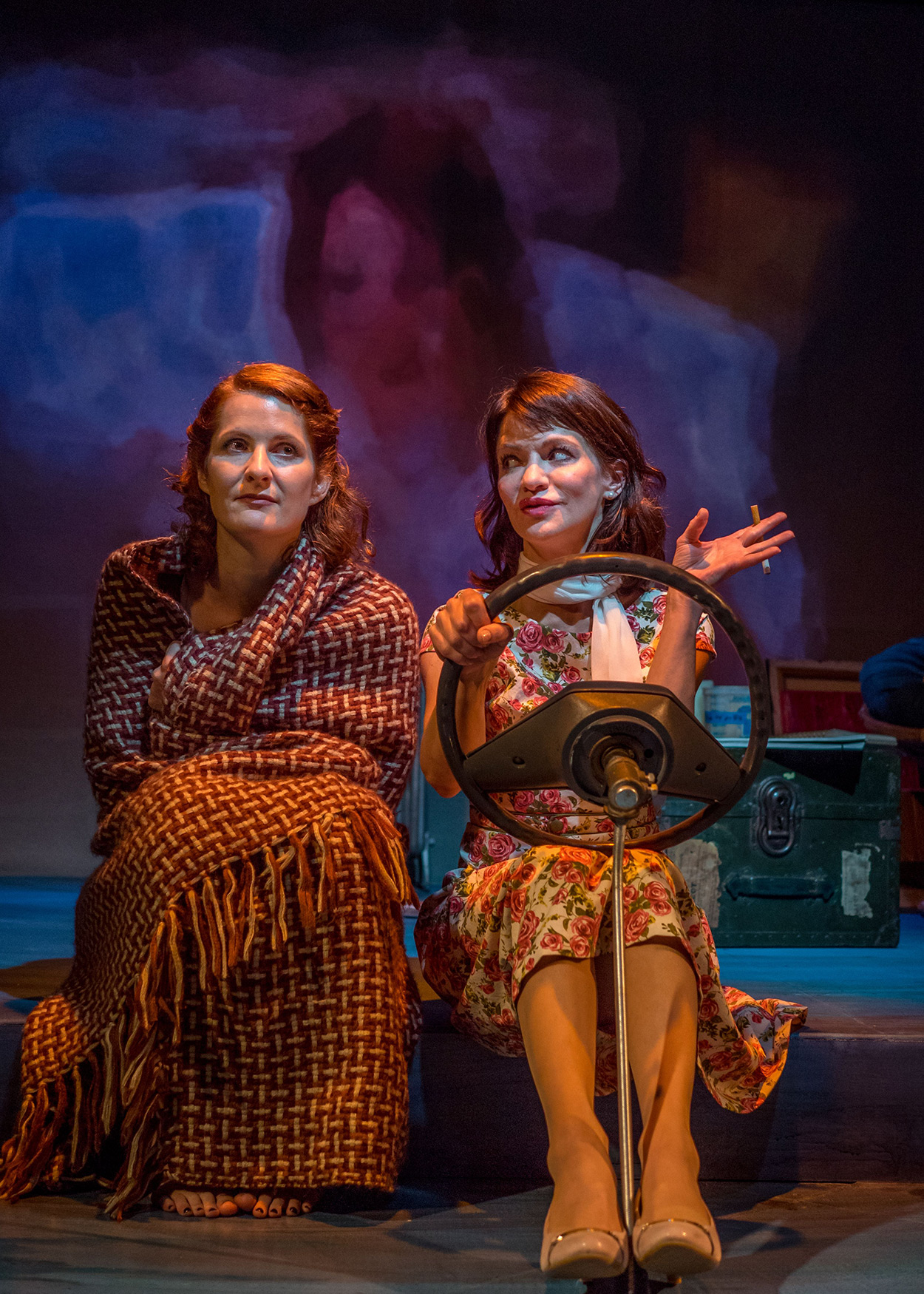 Production Photo from Janice Underwater (2014). Two women sit side-by-side. The woman to the left is wrapped in a blanket. The woman to the right is holding a car sterring wheels, depicting the women are in a car.