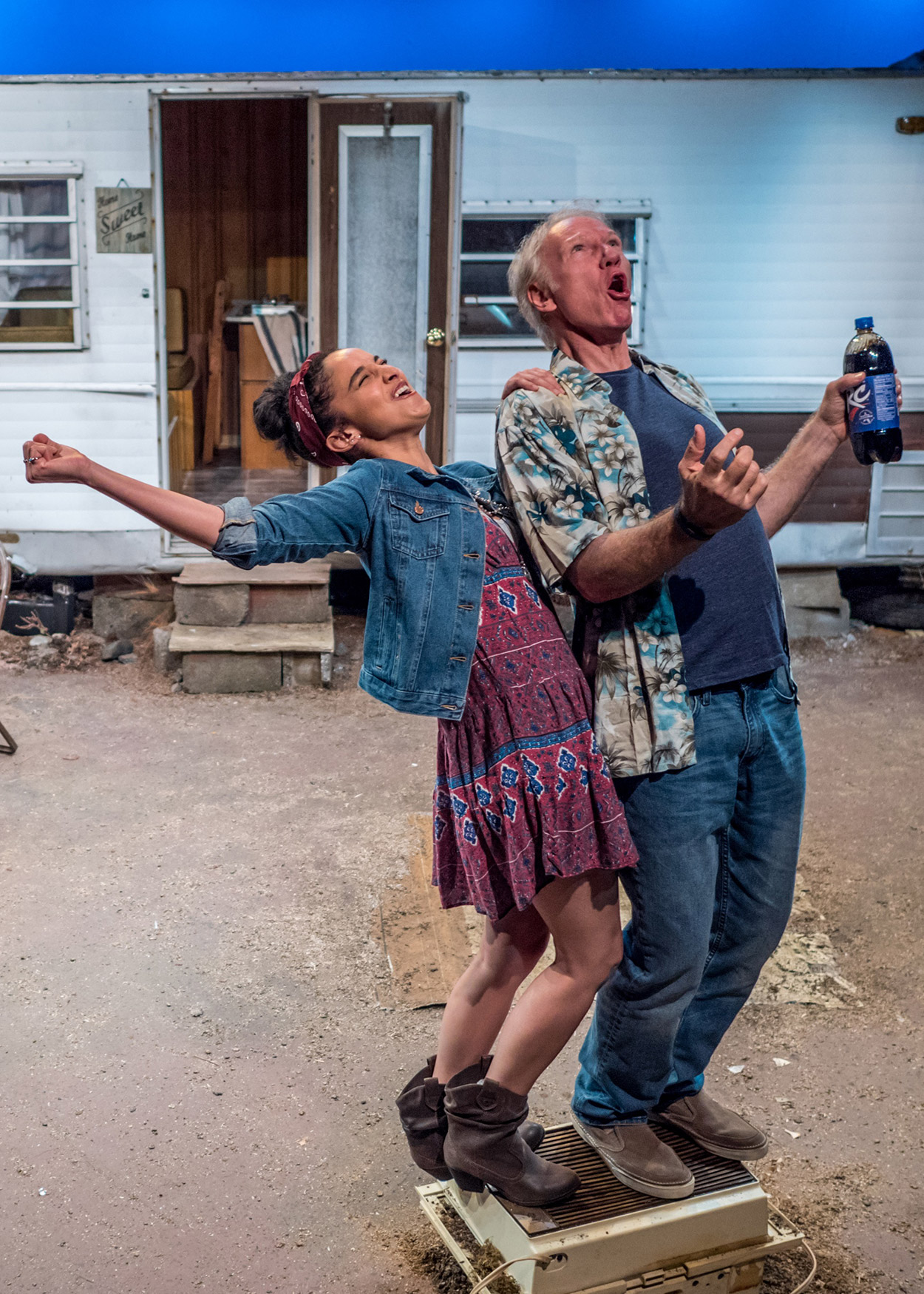 Production Photo from Las Cruces (2016). Set in the desert, a small silver mobile home is at the background. A young woman and an older man stand on an old air conditioning unit, howling up to the sky.