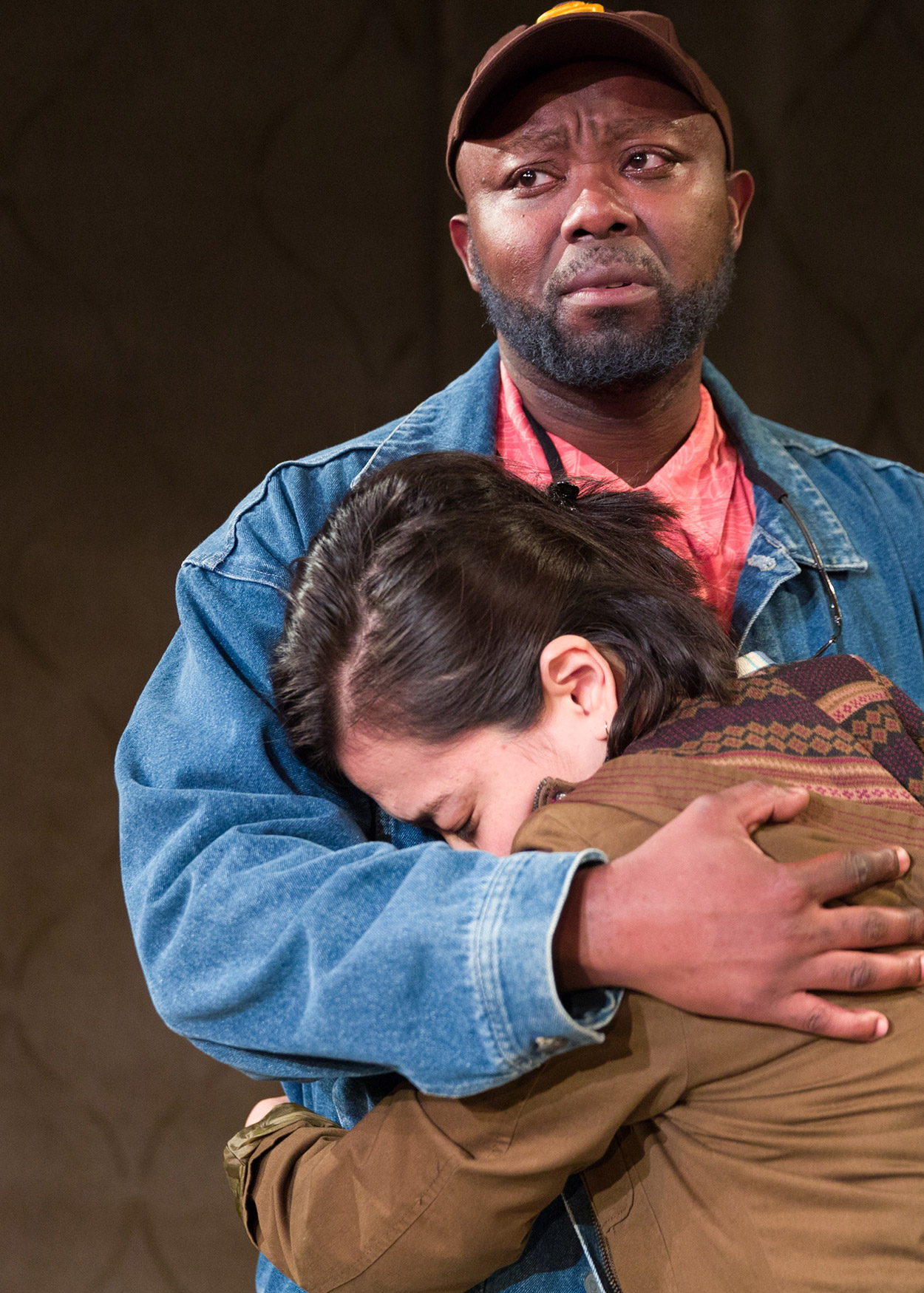 Production Photo from Water by the Spoonful (2016). A Black man with a scruffy beard, wearing a blue jean jacket and brown baseball cap emabraces a woman wearing a brown coat.