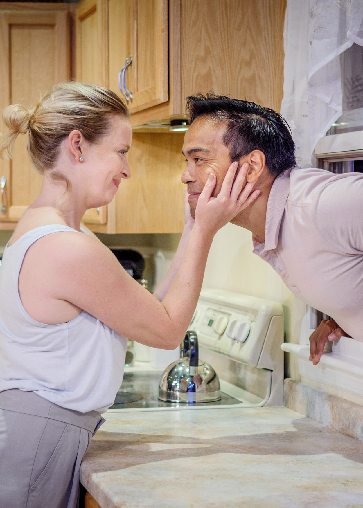 Production Photo from Foster Mom (2017). A woman stands in a kitchen and embraces the face of an man who is looking into the kitchen from a window over the sink.