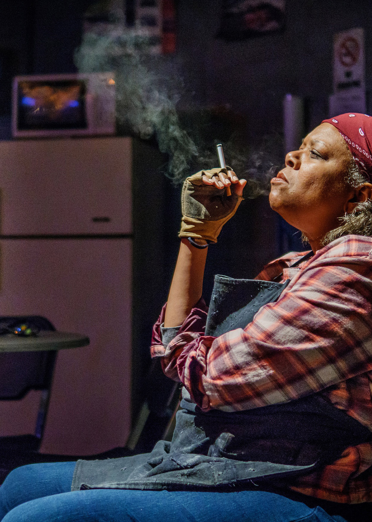 Production Photo from Skeleton Crew (2017). A black woman sits in a dark room smoking a cigarette. She is wearing blue jeans, a gray apron, a red plaid shirt and a red bandana over her hair.