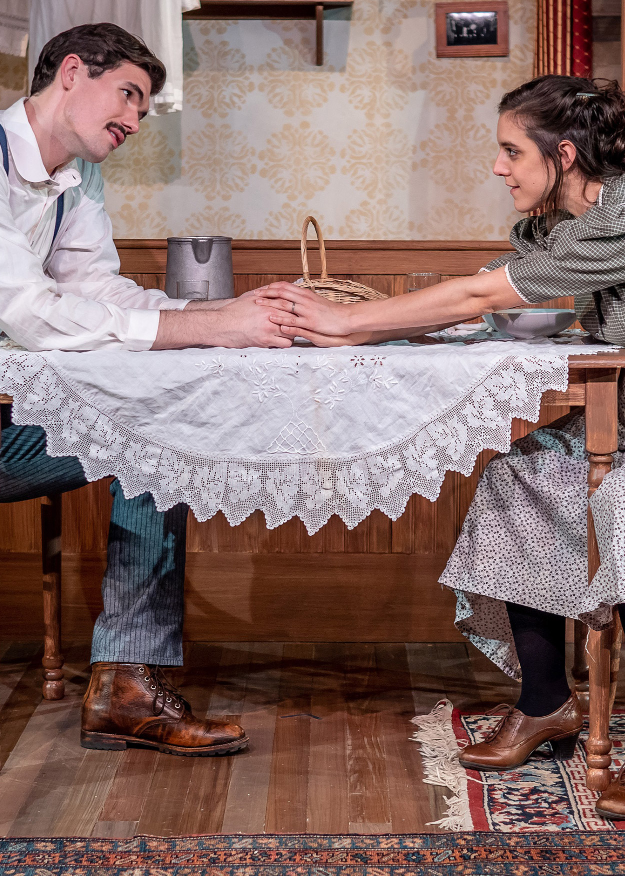 Production photo from Black Tom Island (2018). The play is set in 1916. A man and a woman sit at opposite sides of a table and lean towards each other to hold hands. The man is wearing a white shirt, blue pants and blue suspenders. The woman is wearing a black and white checkered dress and a patterned appron.