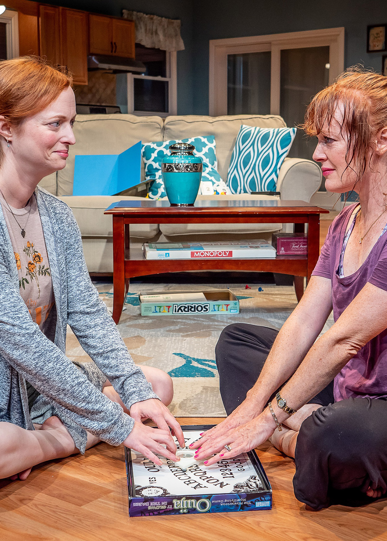 Production photo from The Wake (2019). Two red-haired woman sit on the floor in a living room. Between them, on the floor, is a Oujia board.