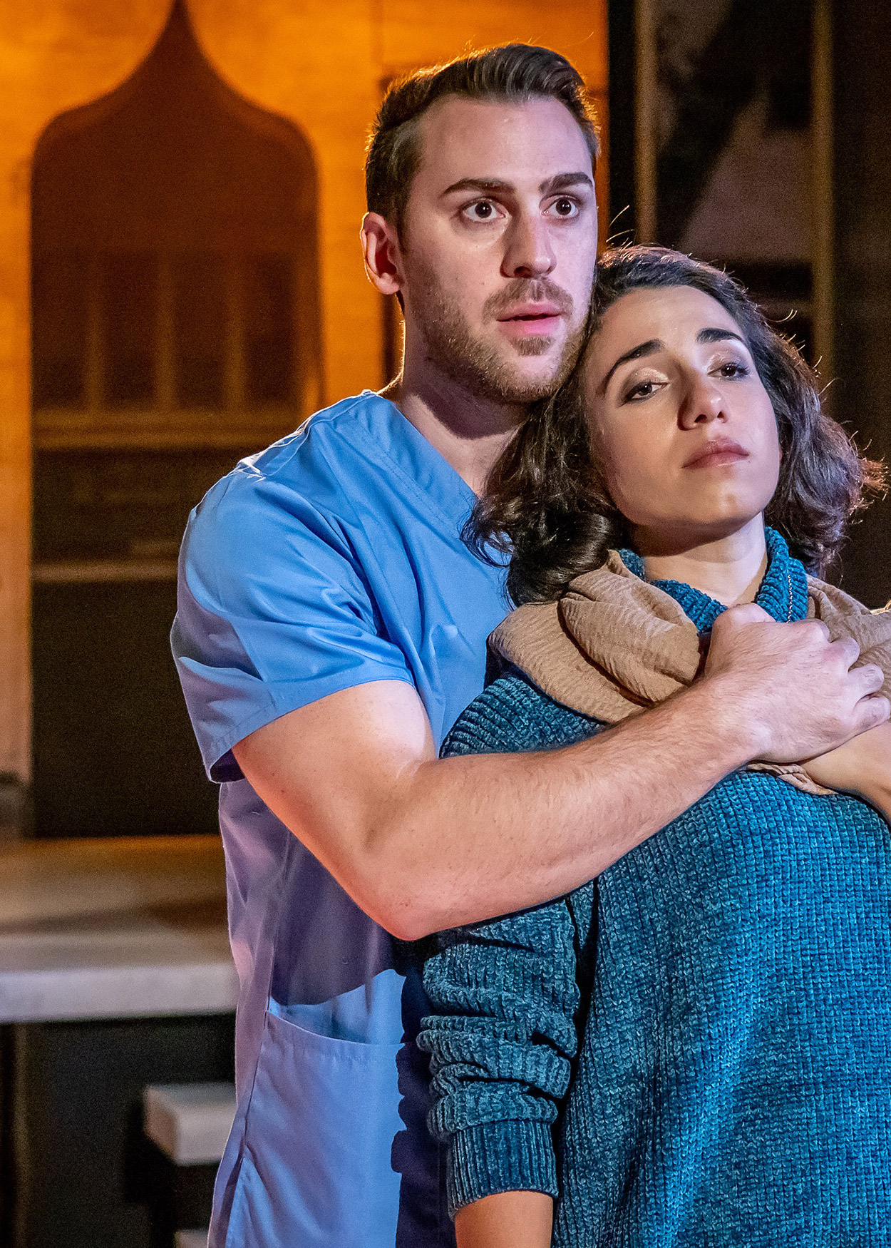 Production Photo from Yasmina's Necklace (2019). A man wearing a blue t-shirt stands behind a woman wearing a blue sweater, embracing her.