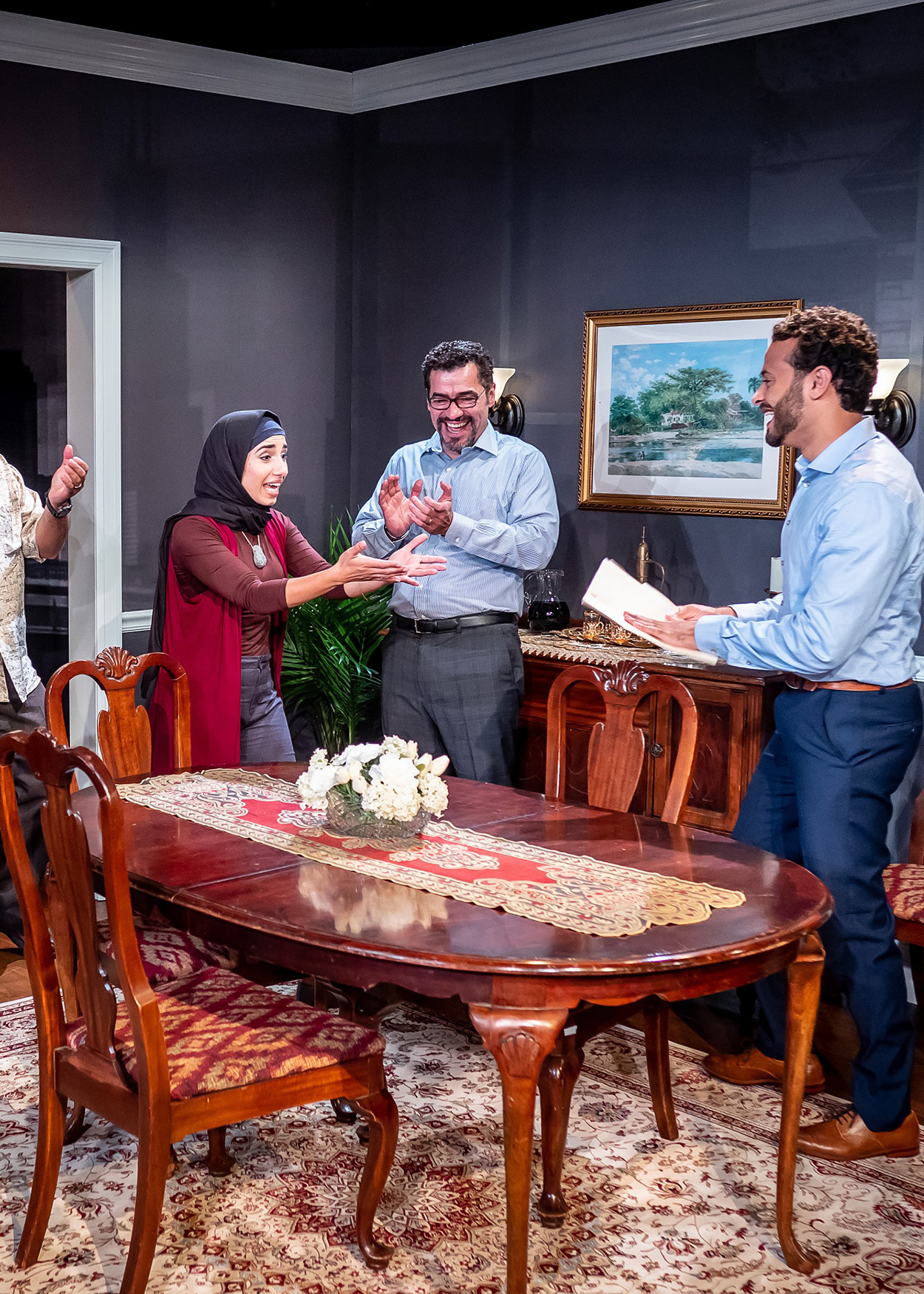 Production Photo from Yasmina's Necklace (2019). Four men and two women stand around a dining room table. Both women are wearing hijabs. One man is handing the younger woman a piece of paper. Everyone present is very excited.