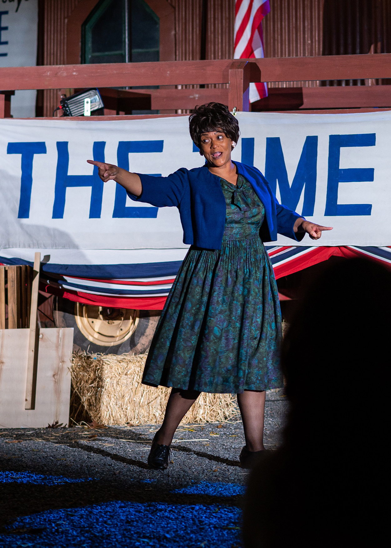 Production photo from Fannie Lou Hamer, Speak On It! (2020). Actress Rema Webb portrays civil rights activistFannie Lou Hamer. Behind her is a sign that reads The Time is Now.
