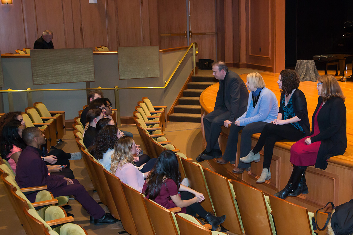 Four adults sit on a stage in a theatre and talk to a group of students sitting in the audience