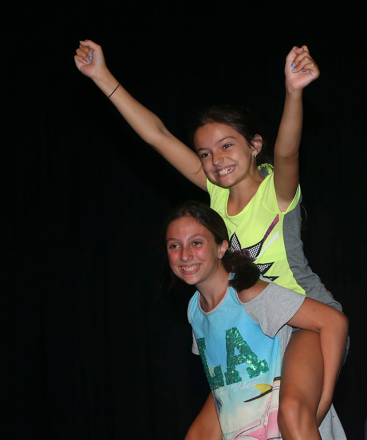 A young girl happily carries another, joyful young girl on her back.