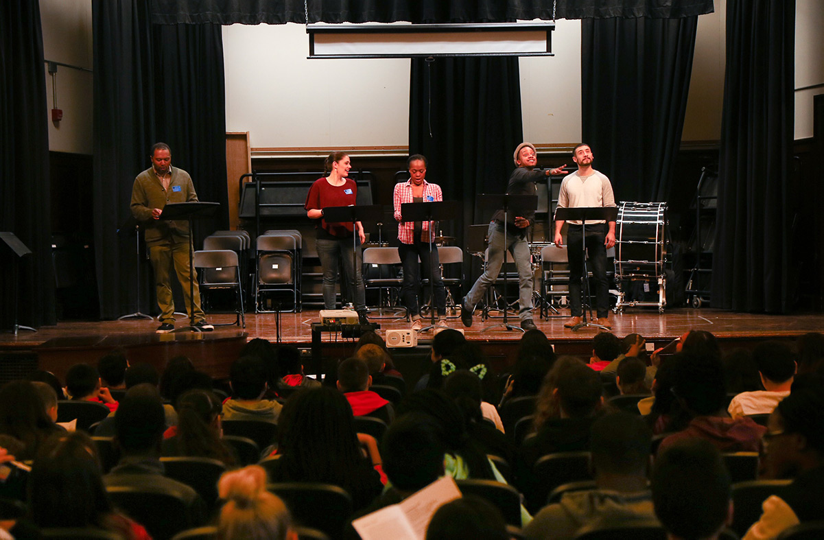 Two actors perform a play while the student writers watch