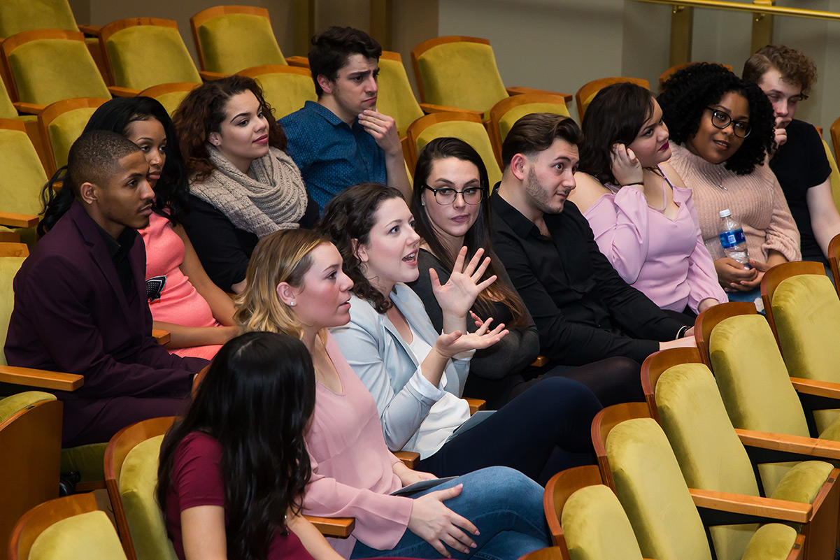 Students are sitting in a theater auditorium.