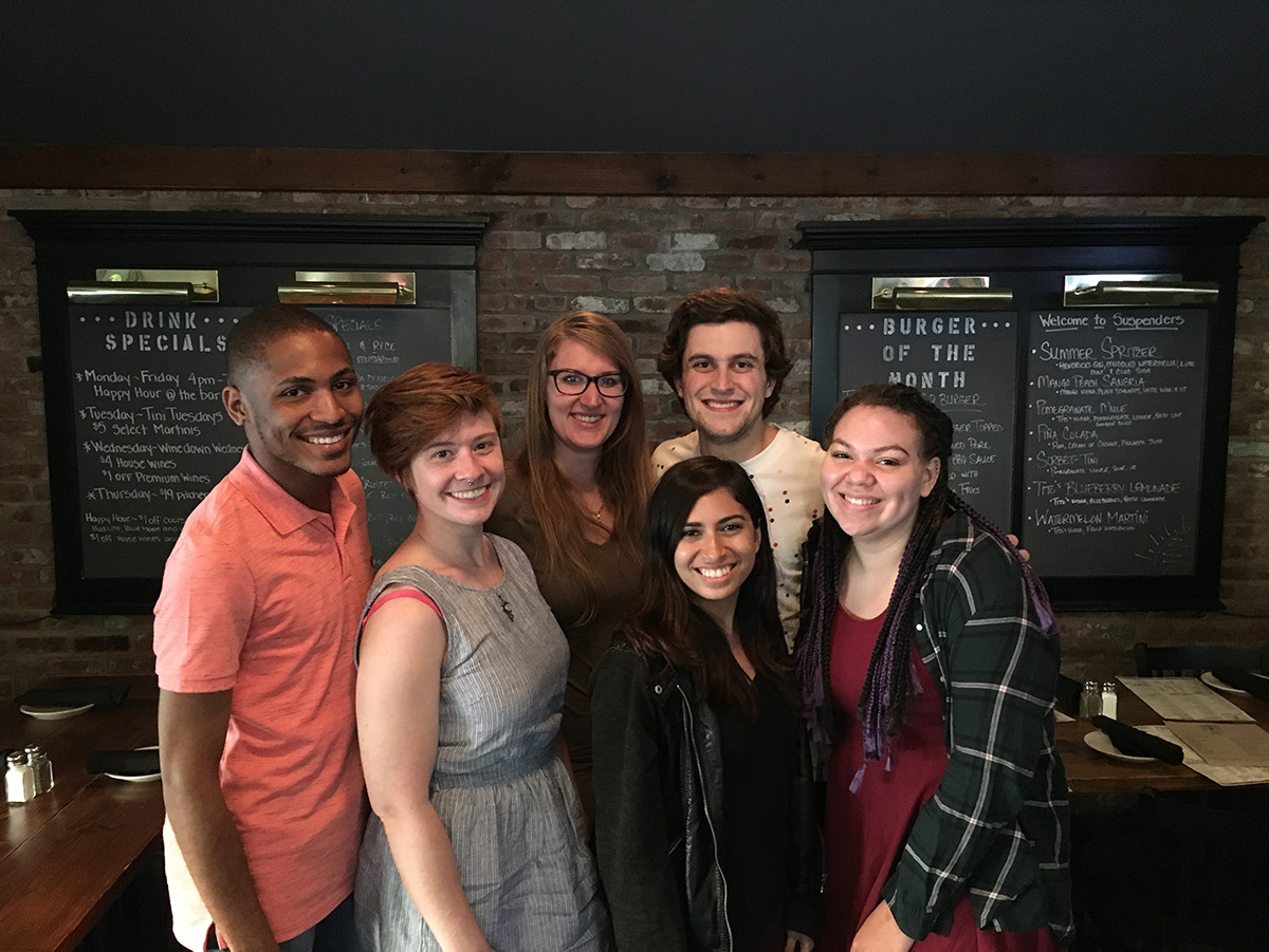 A group of smiling interns enjoy a break at a local restaurant