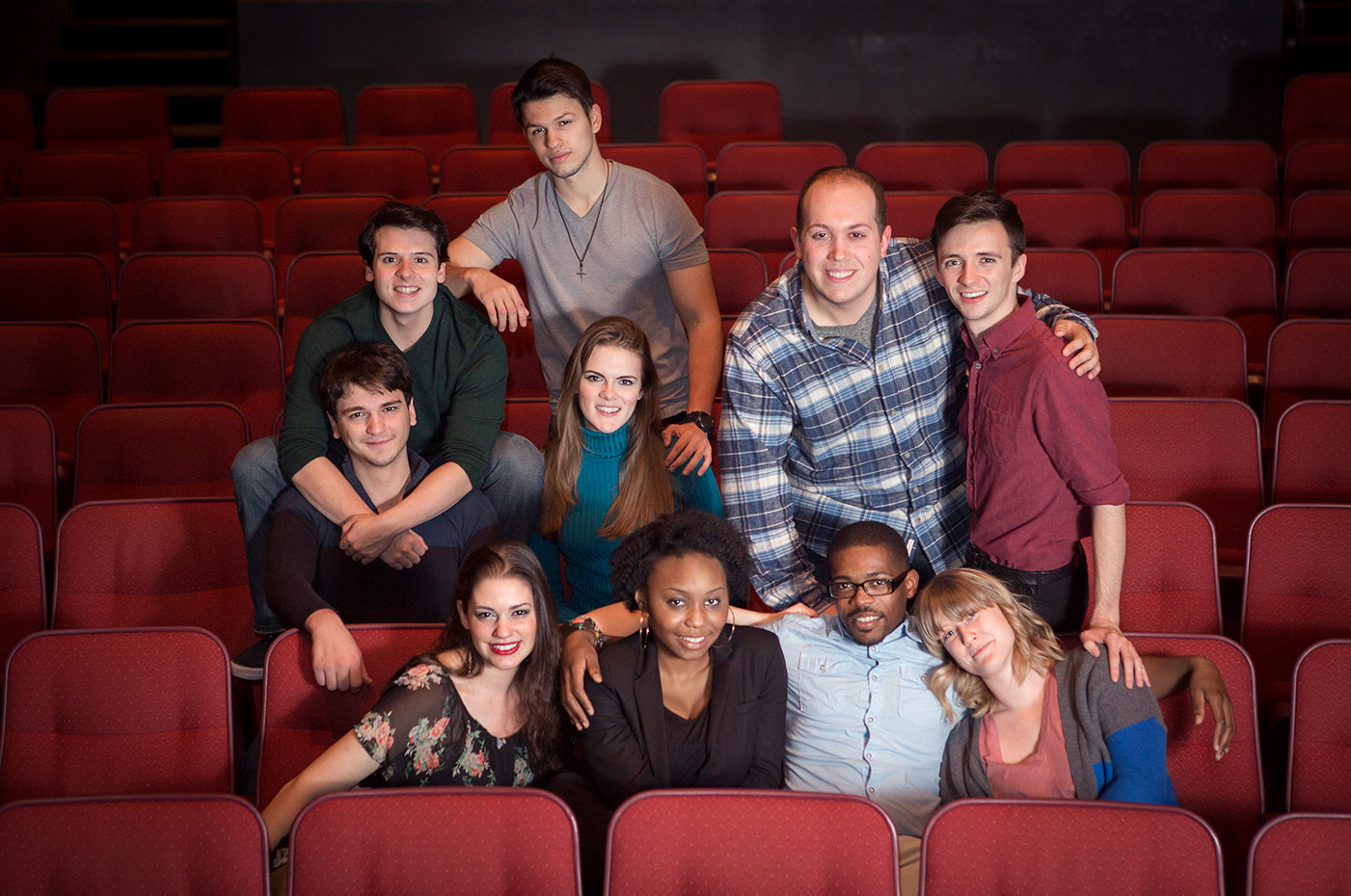 Group of young adults sit in a theatre amongst red chairs, posing for the camera
