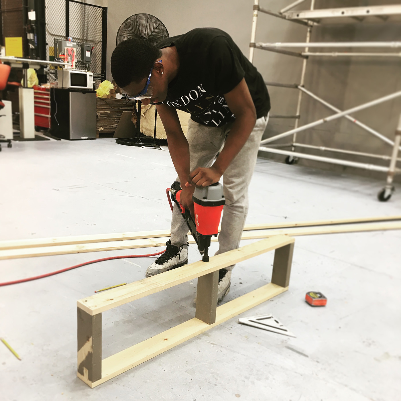 An intern uses a power tool to build a set piece